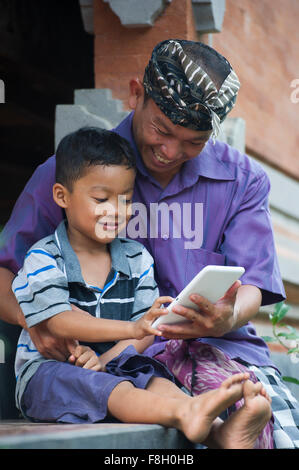 Asian father and son using cell phone outdoors