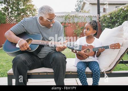 African American grand-père-fille d'enseignement à jouer de la guitare Banque D'Images