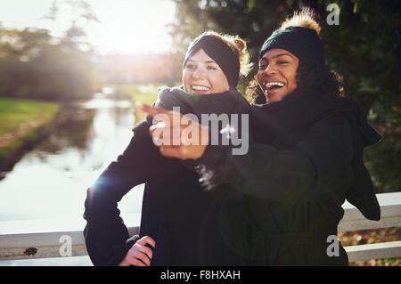 Deux copines de rire de quelque chose alors qu'il se trouvait dans le parc contre de rivière. Banque D'Images