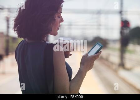 Mid adult woman en attente à la gare, l'utilisation de smartphone, holding Coffee cup Banque D'Images
