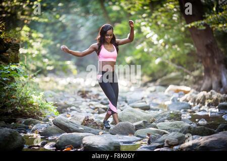 Young female hiker enjambant la rivière forêt rocks Banque D'Images