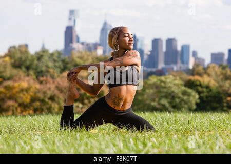 Vue avant du jeune femme à genoux sur l'herbe qui s'étend de la jambe en position de yoga, à l'écart, Philadelphia, Banque D'Images