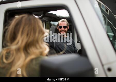 Au cours de l'épaule du jeune femme chat à ami en jeep Banque D'Images
