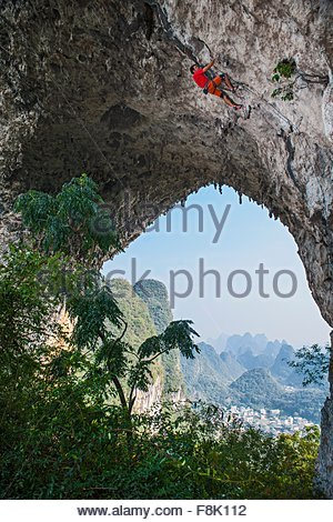Low angle view of male climber climbing l'itinéraire fou sur Moon Hill dans Yangshuo, Guangxi Zhuang, Chine Banque D'Images