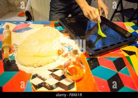 Huiler les mains de womans de cuisson sur table de cuisine Banque D'Images