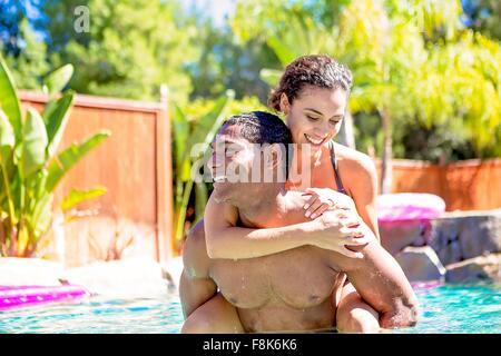 Mid adult man carrying young woman on retour dans la piscine à l'écart smiling Banque D'Images