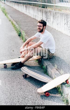 Young man sitting on curb avec trois planches à roulettes Banque D'Images