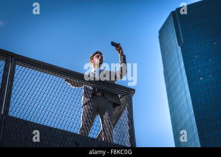 Low angle view of young businessman taking sur smartphone selfies sur balcon-ville, New York, USA Banque D'Images
