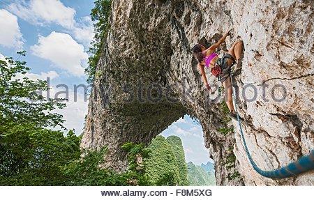 Grimpeur femelle grimper sur la colline de la Lune arche calcaire dans Yangshuo, Guangxi Zhuang, Chine Banque D'Images