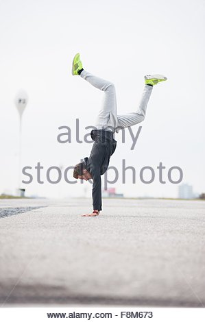 Young male runner doing handstand in sport arena Banque D'Images