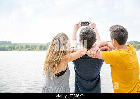 Trois jeunes adultes taking self portrait en utilisant smartphone, vue arrière Banque D'Images