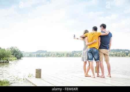 Trois jeunes adultes standing on Jetty, taking self portrait, à l'aide de smartphone, vue arrière Banque D'Images