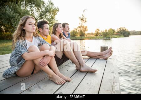 Groupe d'amis sitting on Jetty, relaxant Banque D'Images