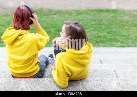 Les jeunes femmes avec des écouteurs sur les étapes de repos Banque D'Images