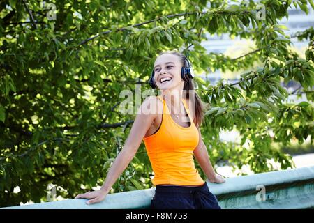 Happy young female runner listening to headphones Banque D'Images