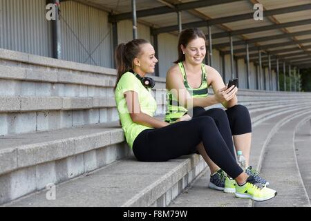 Deux jeunes dames discutent dans des sièges de stade