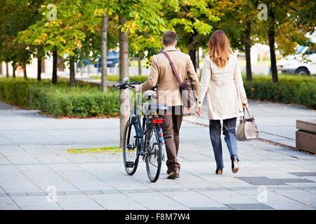 Businessman et woman pushing bike