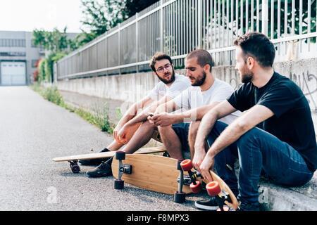 Side view of young Men sitting on curb avec planches à roulettes Banque D'Images