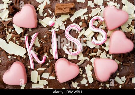 Still Life de chocolats en forme coeur rose avec le mot kiss in candy rose rayures Banque D'Images