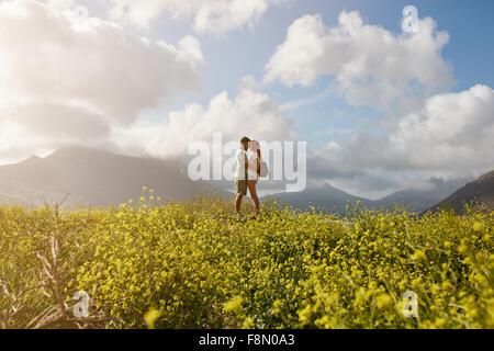 Couple romantique et à la recherche à l'autre, tout en se tenant sur une colline à l'extérieur sur une journée d'été. Banque D'Images