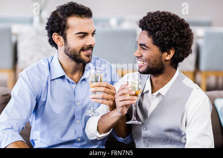 Happy gay couple drinking champagne Banque D'Images