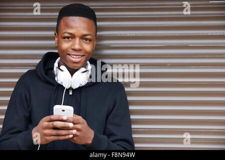 Teenage Boy écouter de la musique et à l'aide de téléphone en milieu urbain Banque D'Images