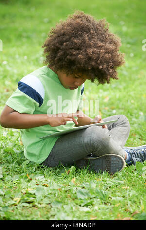 Young Boy Using Digital Tablet In Park Banque D'Images