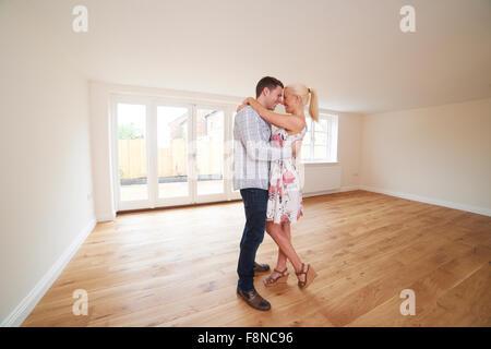 Jeune couple excité en salle vide de leur première maison