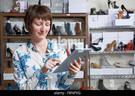 Propriétaire d'entreprise de chaussures en ligne using digital Tablet Banque D'Images
