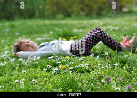 Girl lying on grass in springtime Banque D'Images