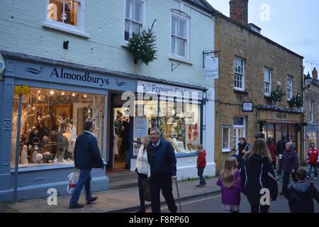 Les gens, y compris les familles avec enfants, des achats de Noël dans la rue bon marché, Sherborne, Angleterre. Banque D'Images