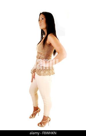 Une très jolie jeune fille debout dans le profil dans le studio pour fond blanc en blanc pantalon de ville avec Banque D'Images
