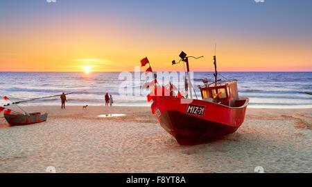 Bateau de pêche sur la plage près de la mer Baltique, Miedzyzdroje, Pologne, au coucher du soleil Banque D'Images