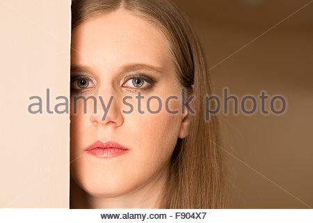 Head shot d'une jeune femme avec son visage partiellement bloqué par un mur. Banque D'Images