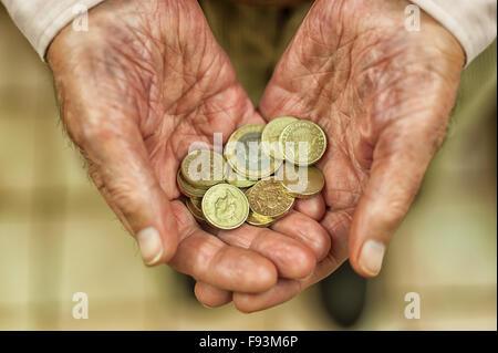 Pièces livre d'or brillant qui s'est tenue à mains montrant toutes les petites économies et appel à l'aide de l'argent Banque D'Images