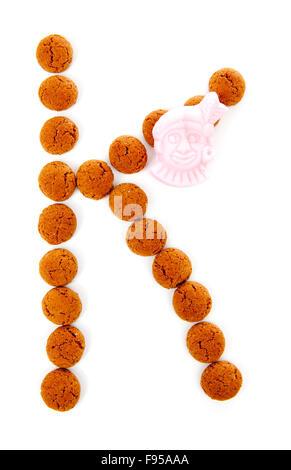 Les écrous de gingembre, pepernoten, en forme de lettre K isolé sur fond blanc. Sinterklaas hollandais typique des Banque D'Images