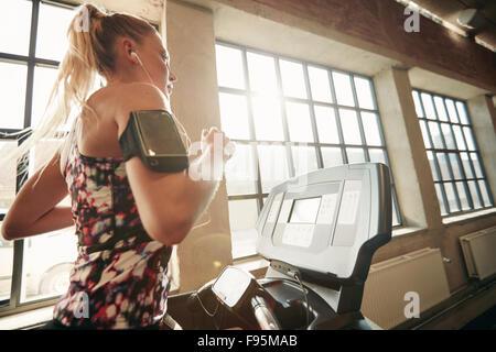 Les jeunes femmes ciblées l'élaboration à la salle de sport le jogging sur un tapis roulant. Femme Fitness faire Banque D'Images