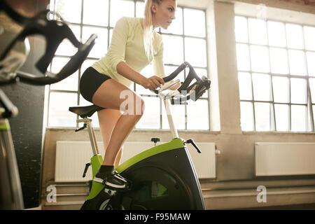 Femme Fitness vélo de spinning à faire de sport. Mettre en place les jeunes filles travaillant sur des vélos de Banque D'Images