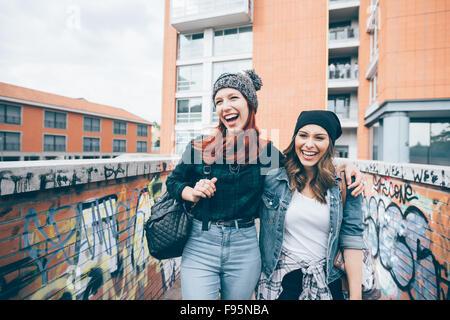 La figure du genou de deux jeunes handsome young Blonde Redhead et les cheveux droits Femmes marchant hugging piscine Banque D'Images