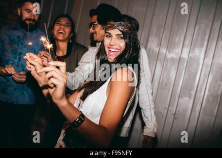 Tourné d'une jeune femme jouant avec des cierges dans la nuit. Best Friends 4 juillet à l'extérieur. Banque D'Images