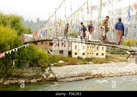 Les villageois chat alors qu'ils traversent un pont suspendu dans la périphérie de Paro, Bhoutan Banque D'Images