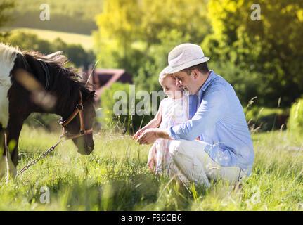 Portrait de jeunes heureux avec son père à l'extérieur, la campagne dauhter poney d'alimentation Banque D'Images