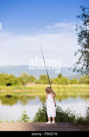 Cute little girl de la pêche sur le lac avec Banque D'Images