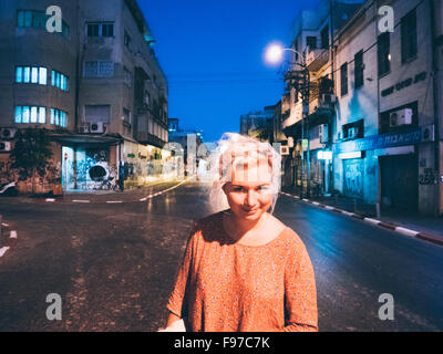 Portrait of Woman Standing On Street at Night Banque D'Images