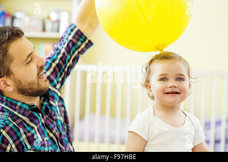Heureux père et sa petite fille jouant à la maison Banque D'Images