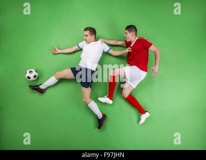 Deux joueurs de football enthousiastes qui luttent pour une balle. Studio shot sur un fond vert. Banque D'Images