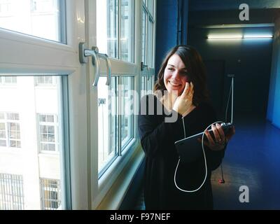 Happy Young Businesswoman With Laptop In Office Corridor Banque D'Images