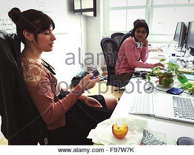 Beau portrait à l'aide de téléphone tout en regardant son collègue In Office Banque D'Images
