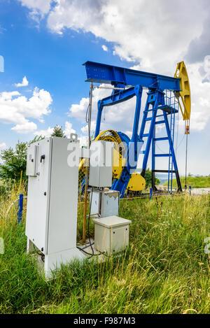 Pompes à huile d'extraction électrique avec PLC cabinet. Paysage de l'industrie du pétrole et du gaz. Banque D'Images
