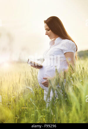 Portrait d'une jeune femme enceinte priant dans le domaine Banque D'Images